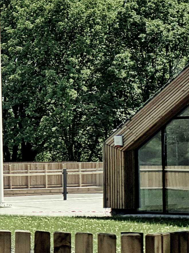 Zdjęcie przedstawia fragment architektury Służewskiego Domu Kultury. Drewniane budynki oraz płot i fragment amfiteatru.